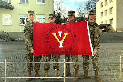 Four cadets hold up a VMI flag in Lithuania